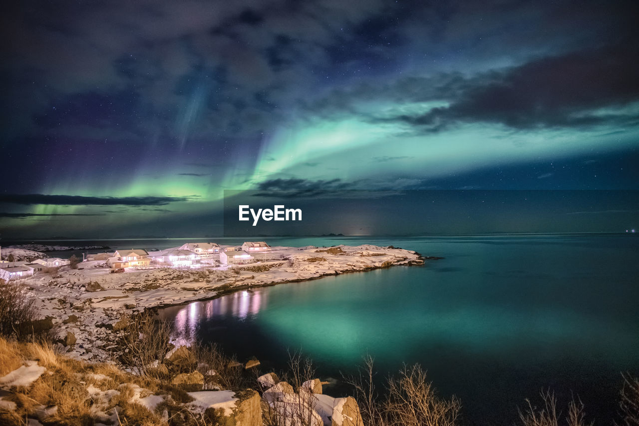 Scenic view of sea against dramatic sky at night