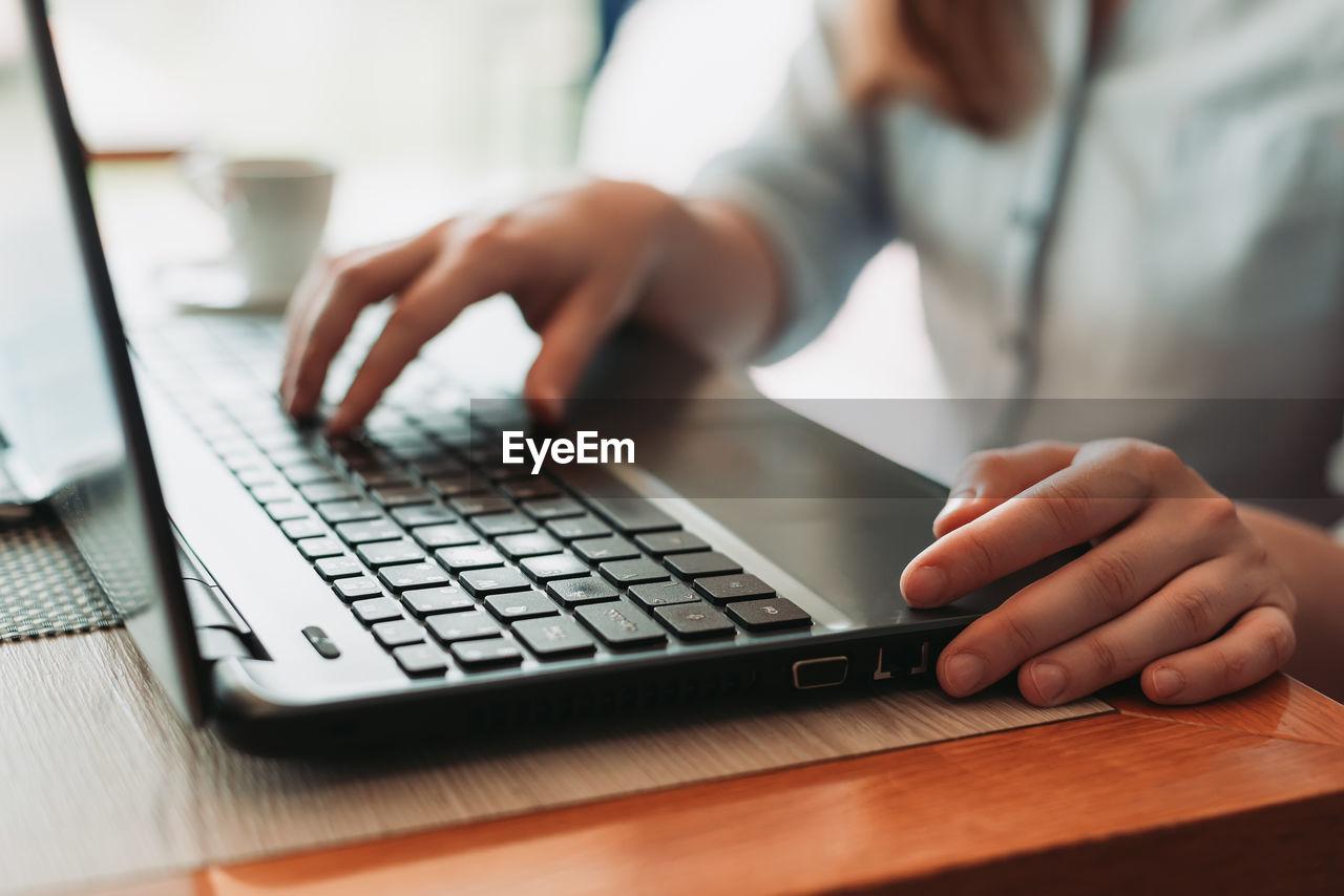 Hands typing on laptop keyboard, freelancer remote work