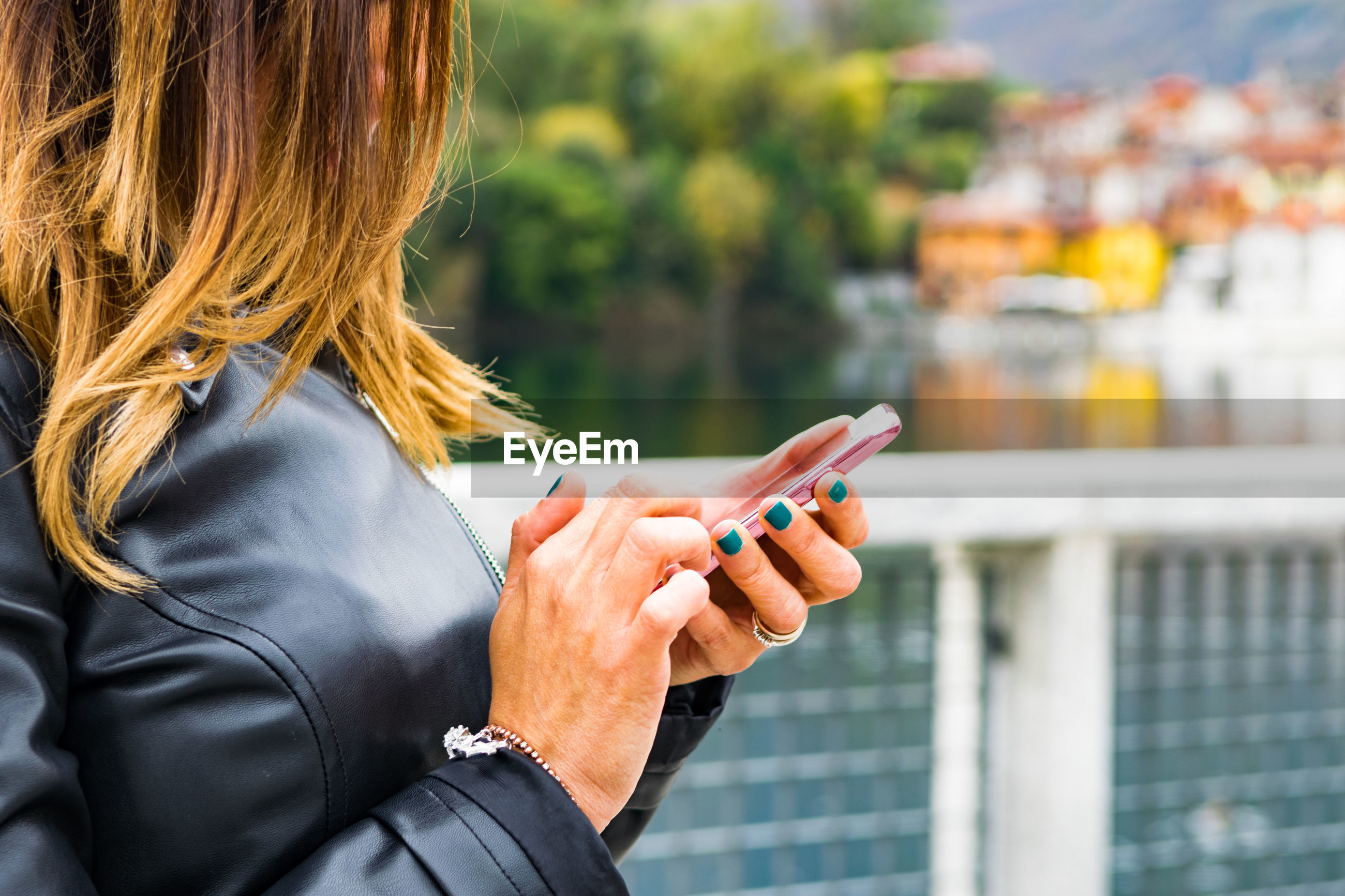 Close-up of woman using mobile phone on bridge