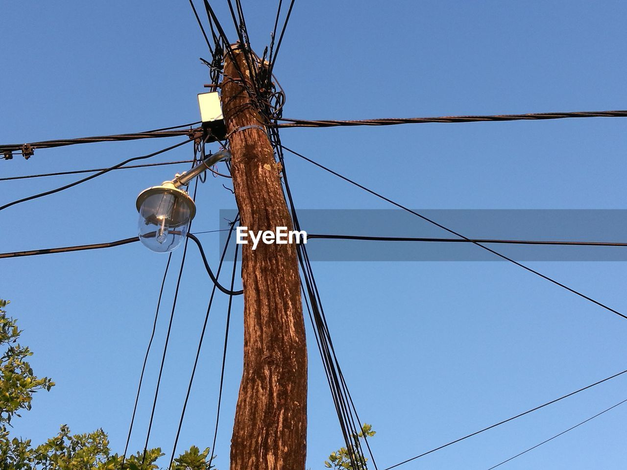 cable, low angle view, electricity, connection, technology, sky, power line, fuel and power generation, power supply, lighting equipment, clear sky, no people, blue, electricity pylon, nature, day, street light, outdoors, pole, complexity, light, telephone line, electrical equipment, electrical component
