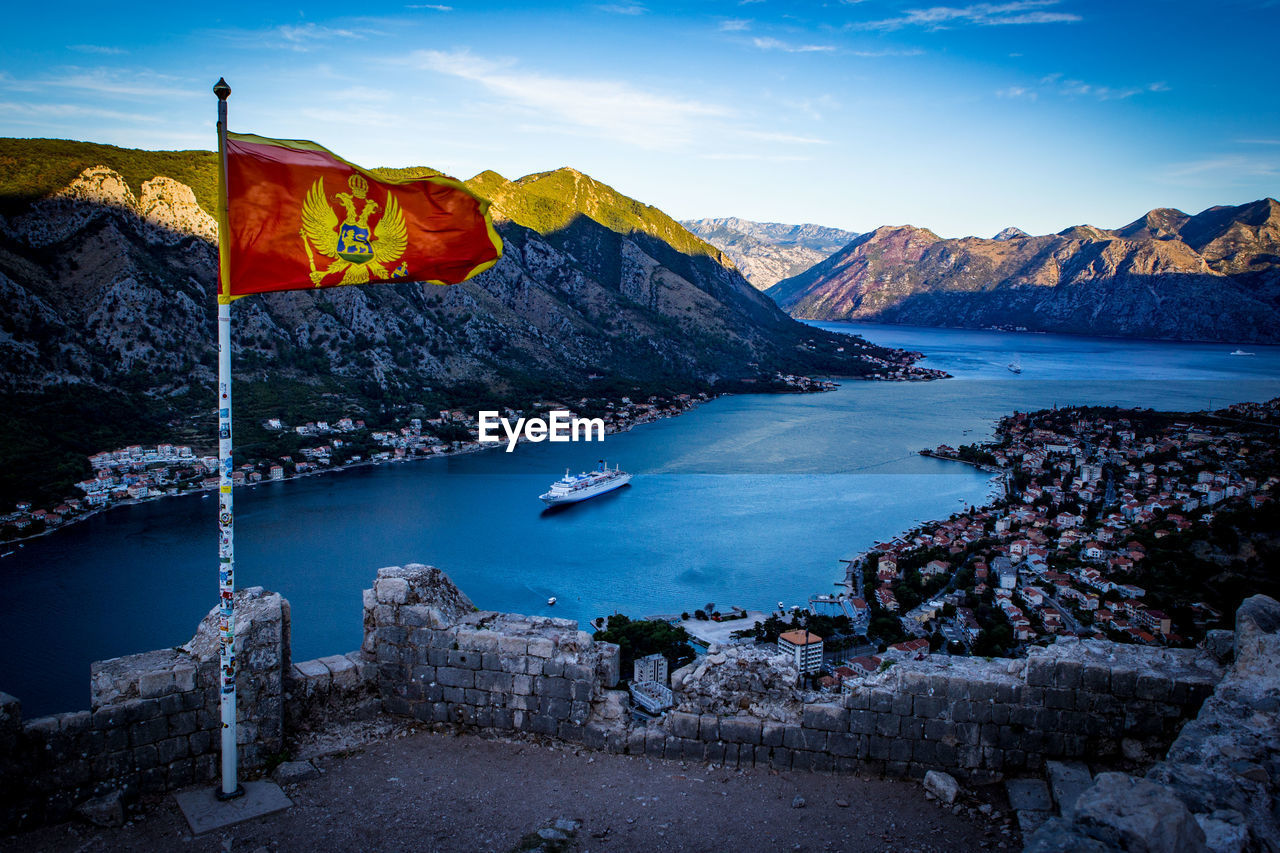 Montenegrin Flag Waving Against River And Mountains