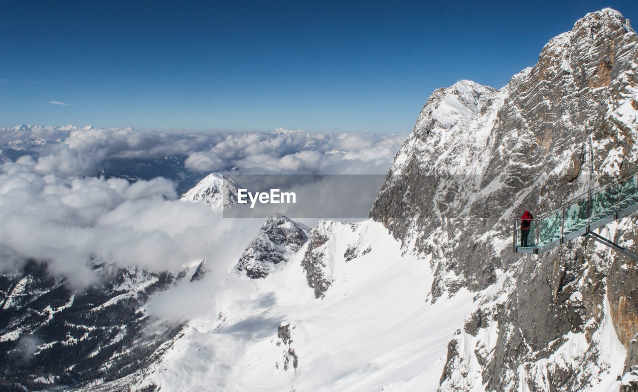 Rear View Of Person Standing On Observation Point By Snowcapped Mountains