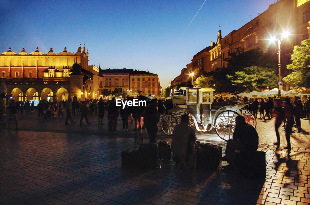 PEOPLE AT ILLUMINATED CITY AT NIGHT