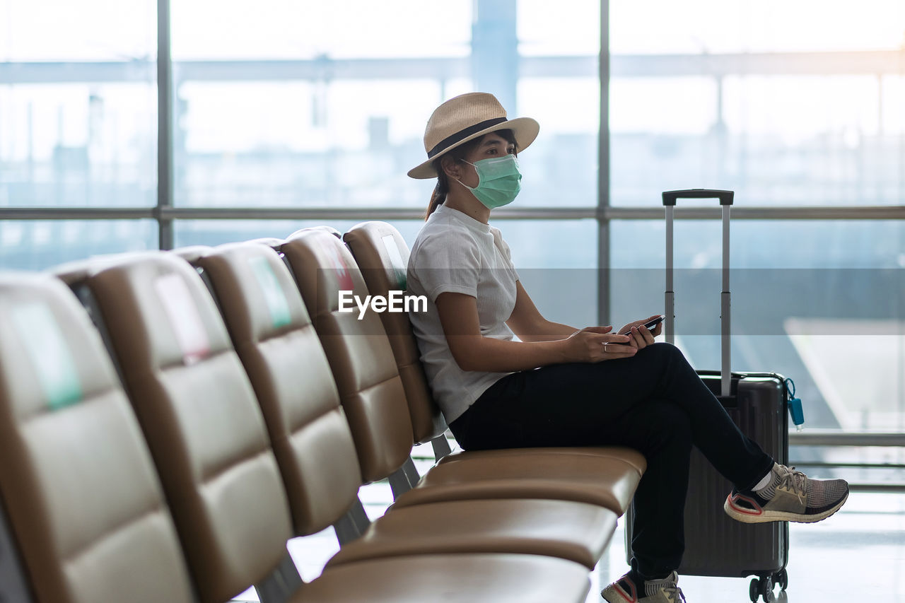 Full length of woman sitting on seat in airport