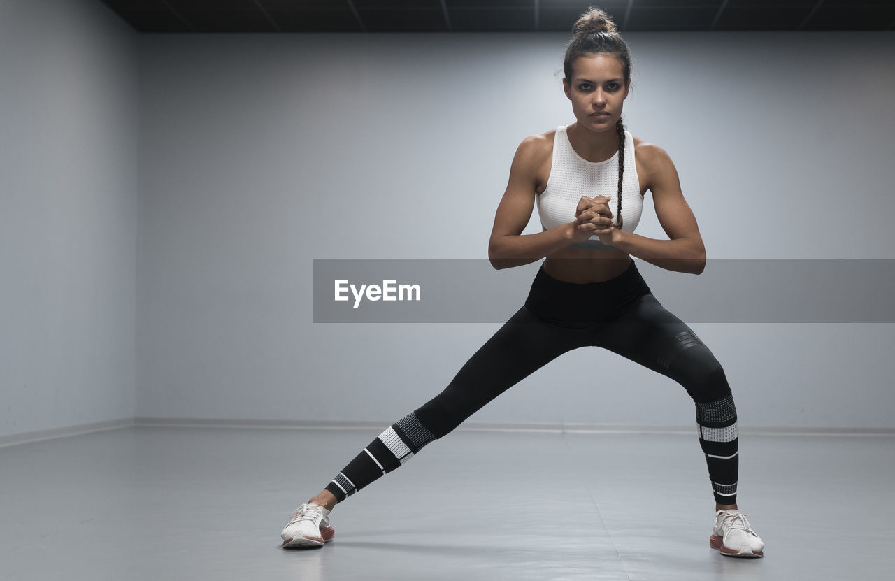 one person, indoors, front view, lifestyles, exercising, full length, looking at camera, portrait, sports clothing, young adult, healthy lifestyle, young women, strength, sports training, standing, leisure activity, sport, women, real people, physical activity