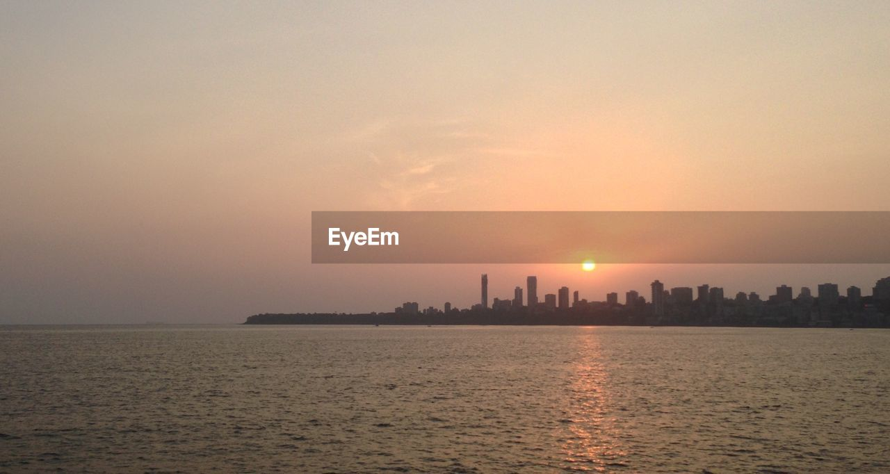 sunset, architecture, built structure, building exterior, skyscraper, cityscape, travel destinations, city, orange color, waterfront, sky, urban skyline, no people, sun, water, silhouette, modern, scenics, nature, outdoors, beauty in nature, illuminated, sea, day