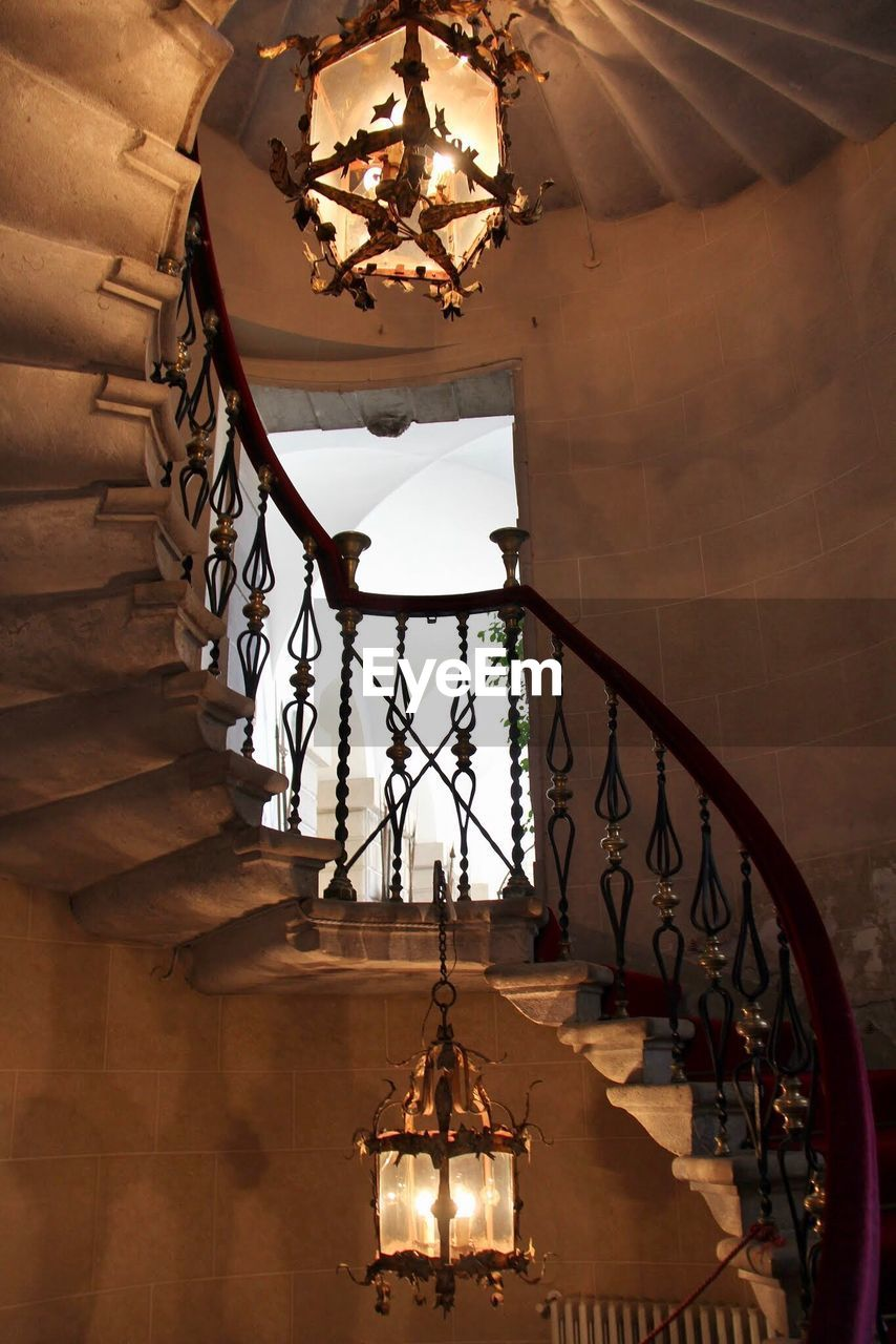 architecture, staircase, built structure, indoors, steps and staircases, railing, low angle view, lighting equipment, building, illuminated, no people, hanging, spiral, spiral staircase, wall - building feature, chandelier, light, absence, nature, ceiling, electric lamp
