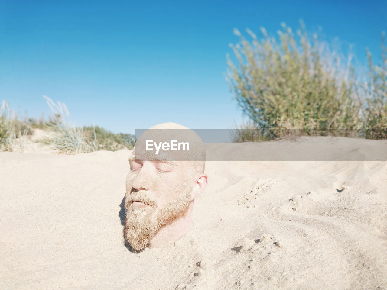 Close-Up Of Man Buried In Sand At Beach Against Clear Sky