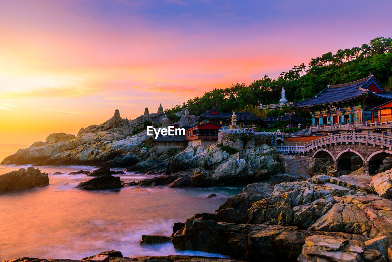 sunset, sky, architecture, built structure, water, building exterior, orange color, building, rock, nature, rock - object, beauty in nature, solid, no people, sea, scenics - nature, waterfront, cloud - sky, travel destinations