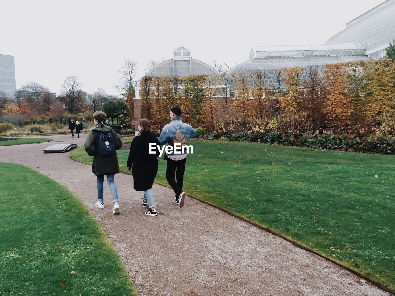 real people, walking, architecture, men, sport, built structure, full length, rear view, leisure activity, outdoors, building exterior, lifestyles, grass, day, clear sky, tree, golf course, nature, sky, people, adult