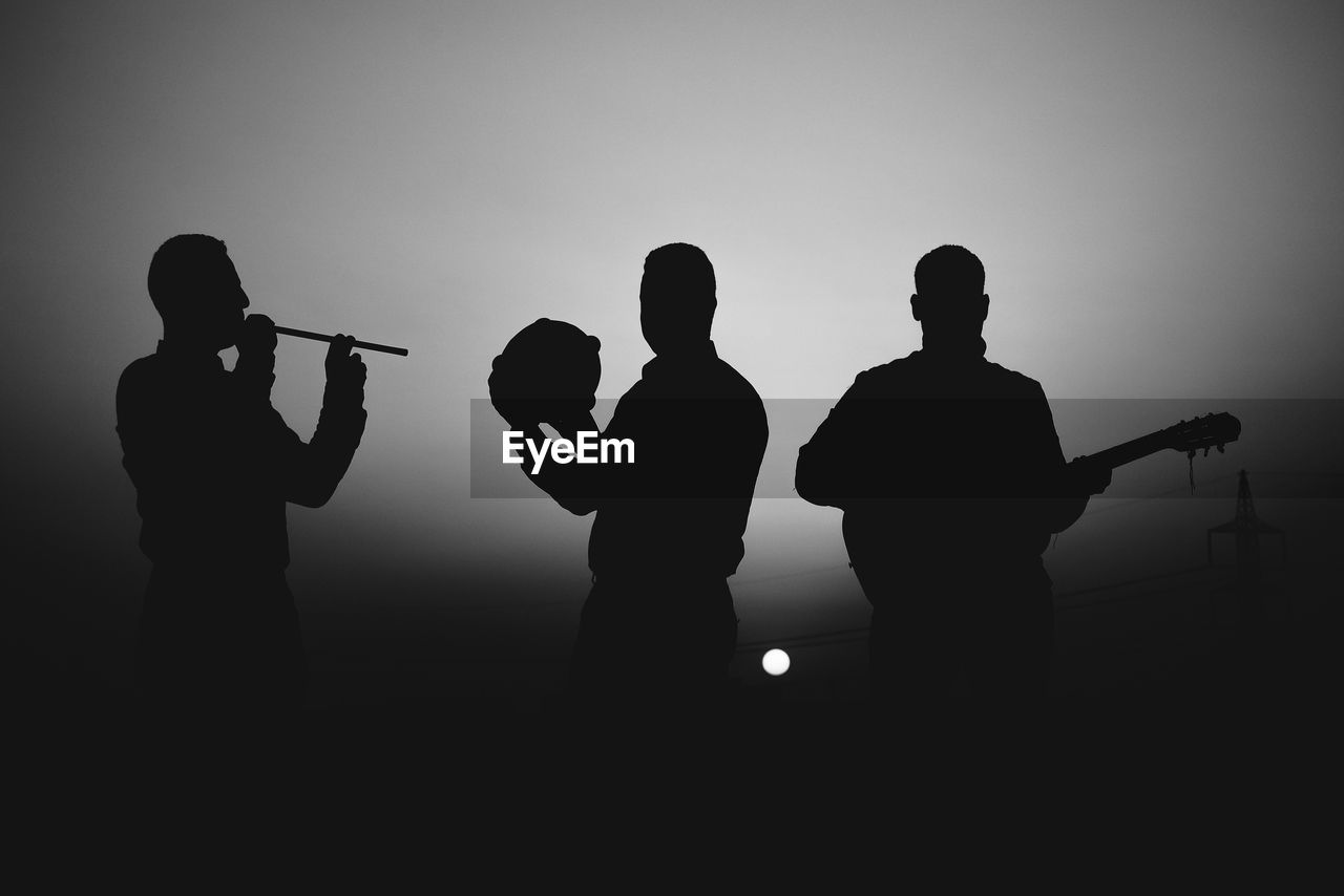 Silhouette People Playing Musical Instruments At Night