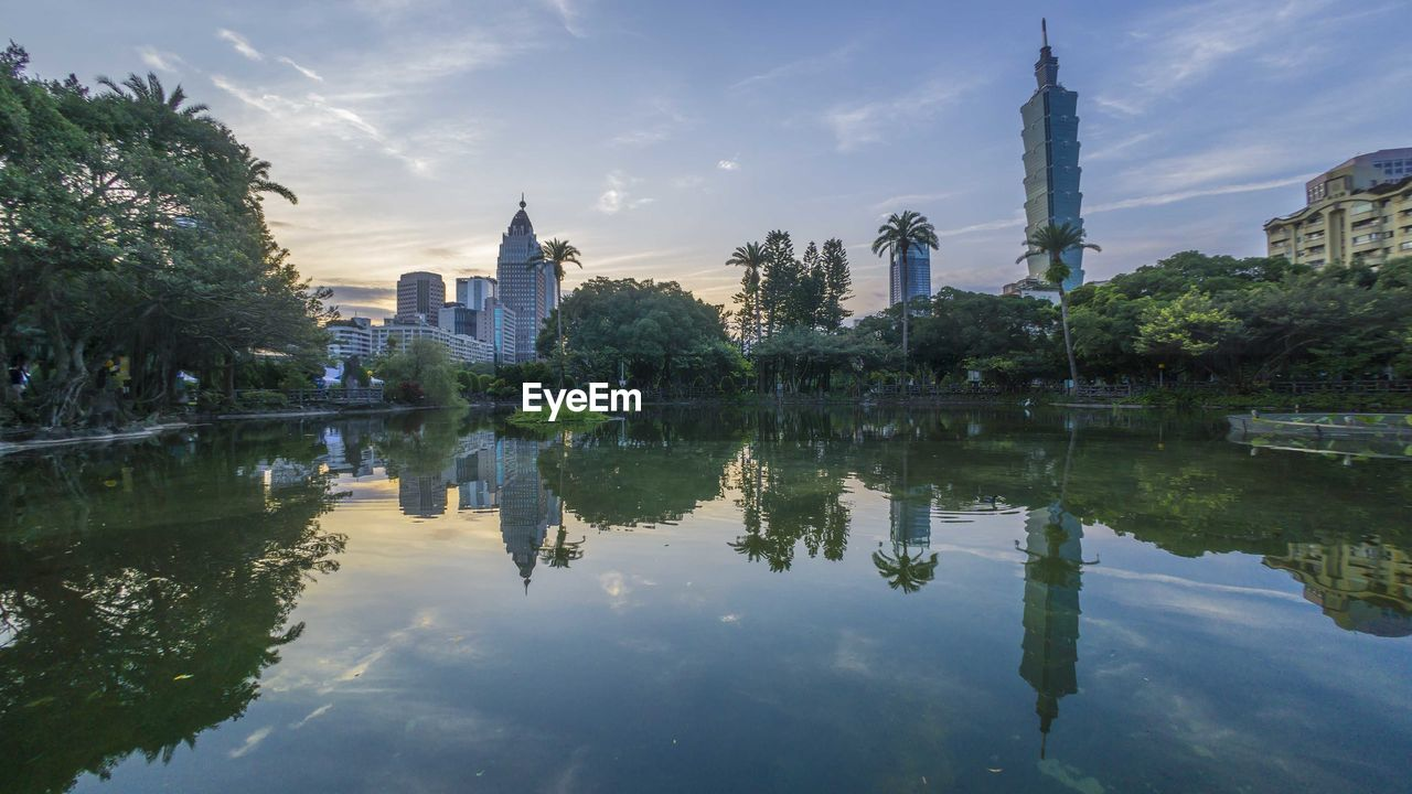 reflection, water, sky, built structure, building exterior, architecture, tree, waterfront, nature, lake, plant, cloud - sky, building, city, travel destinations, no people, travel, tower, place of worship, outdoors, skyscraper