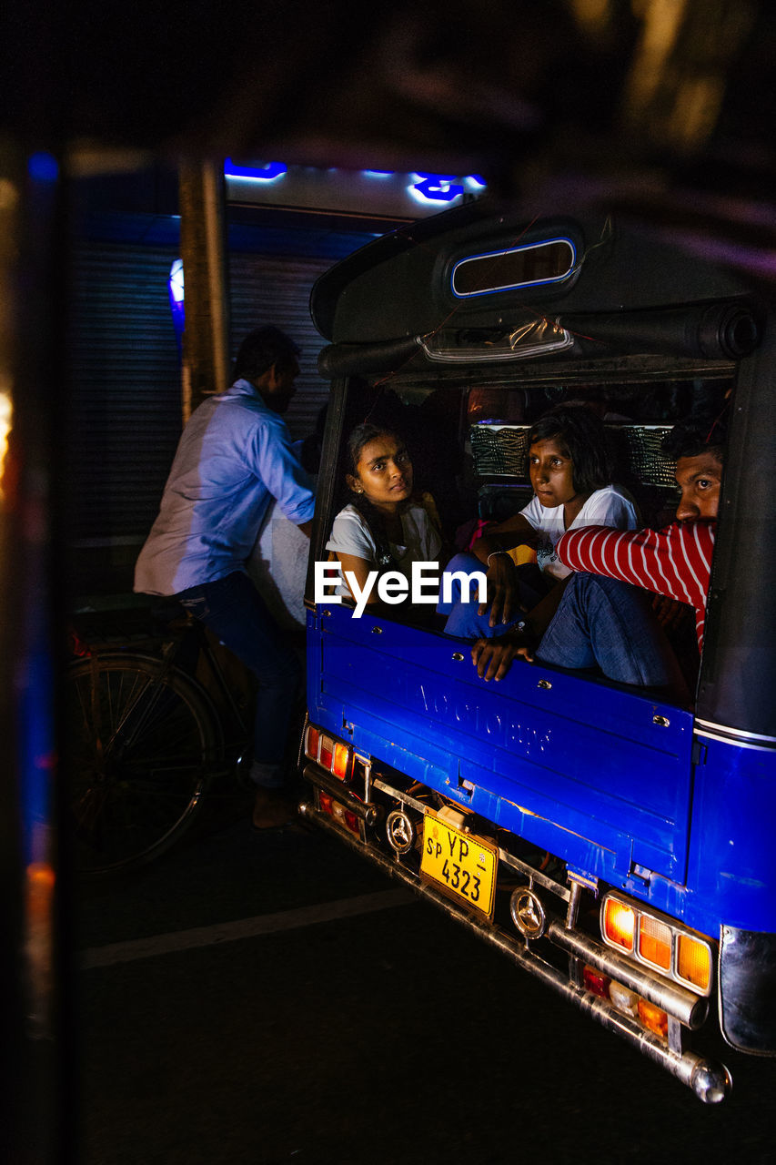 mode of transportation, transportation, car, group of people, land vehicle, real people, men, motor vehicle, night, people, women, sitting, lifestyles, travel, public transportation, adult, leisure activity, females, illuminated, occupation