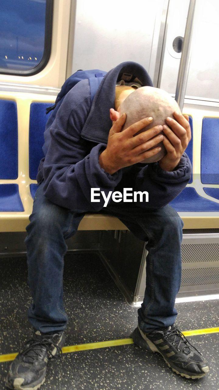 Full Length Of Sad Man Traveling In Train