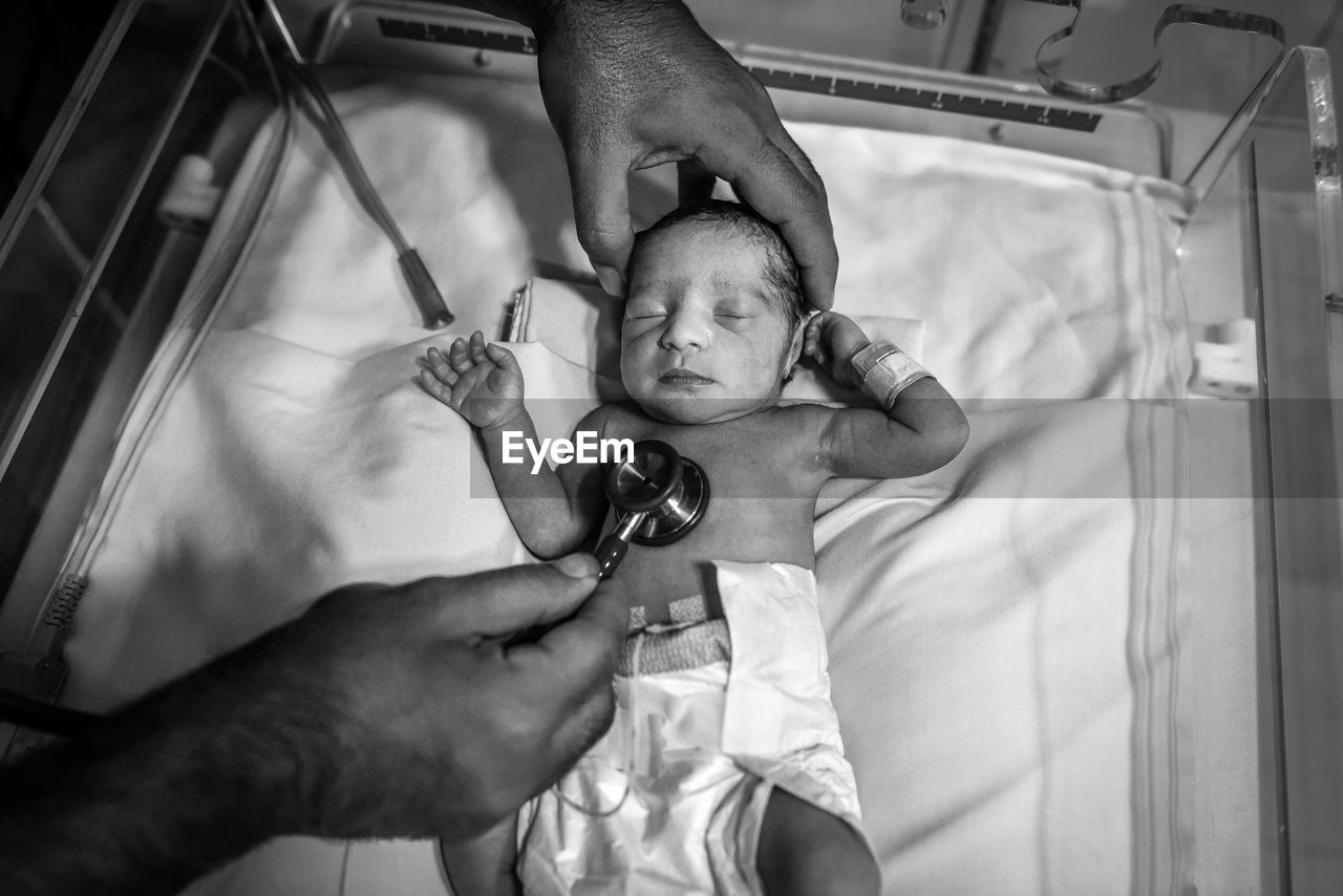 Cropped Hands Of Male Doctor Examining Baby Boy On Bed In Hospital