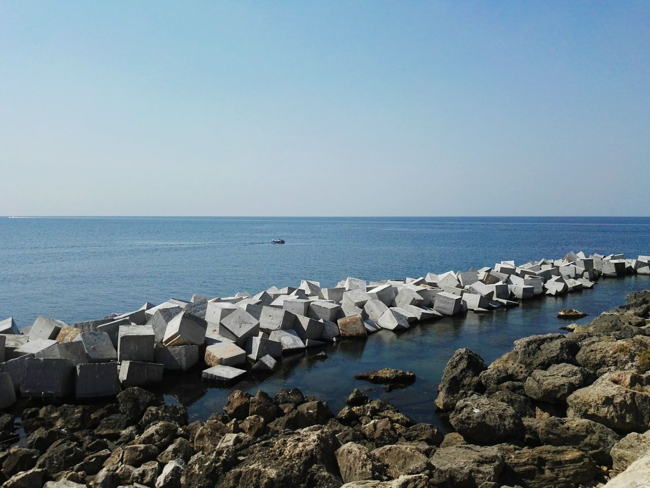 sea, water, sky, horizon over water, horizon, rock, rock - object, beauty in nature, scenics - nature, solid, nature, clear sky, copy space, day, tranquil scene, tranquility, no people, land, beach, groyne