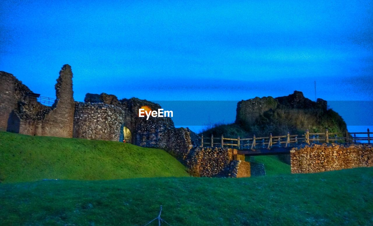 architecture, built structure, castle, history, the past, building exterior, outdoors, no people, day, ancient, blue, nature, grass, sky, beauty in nature