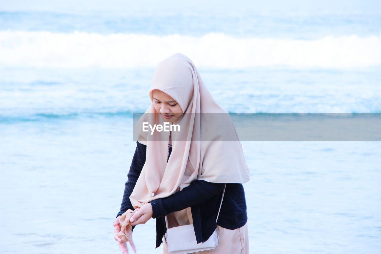 Woman wearing hijab standing against sea