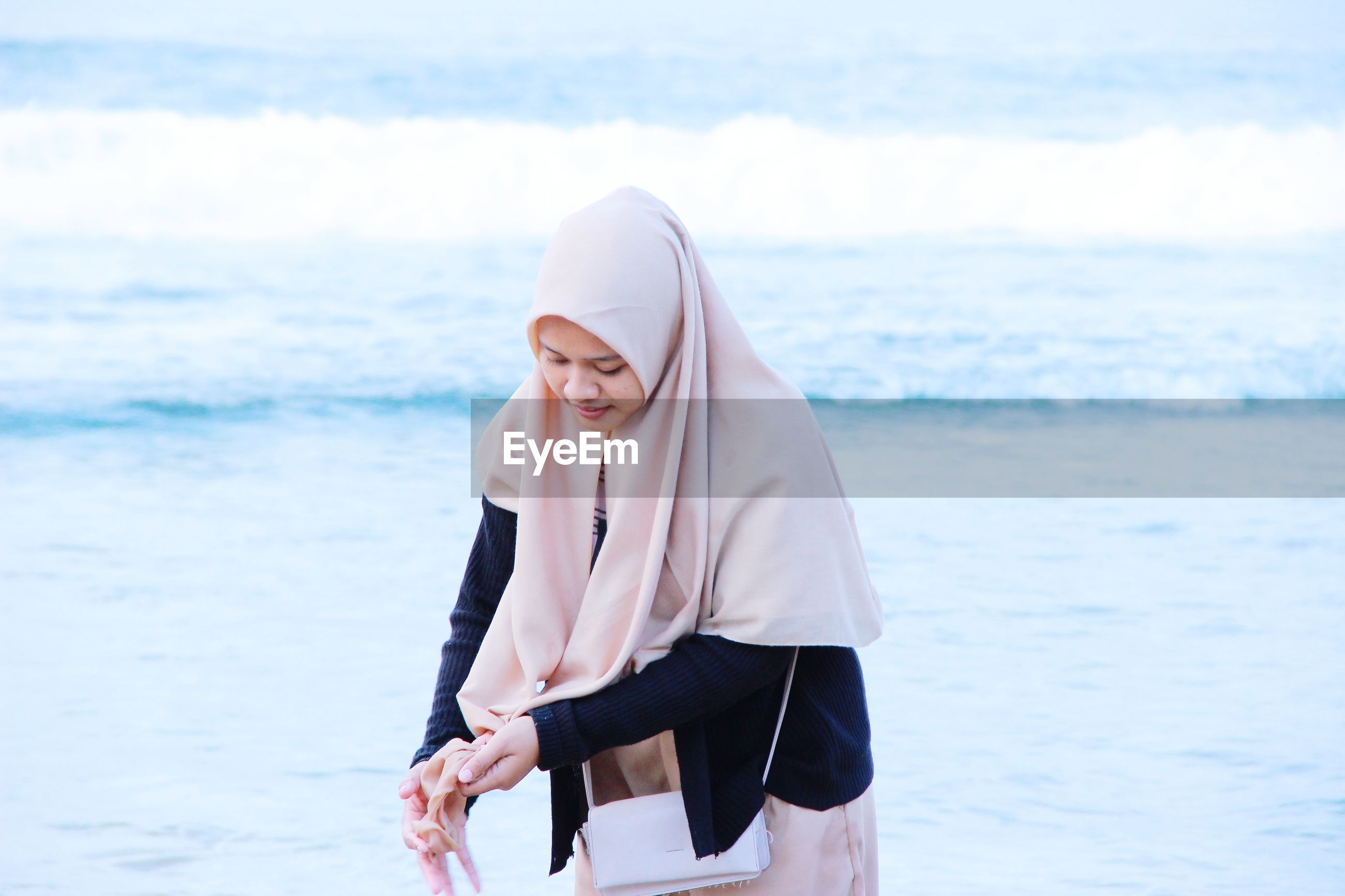 Woman wearing hijab standing against sea
