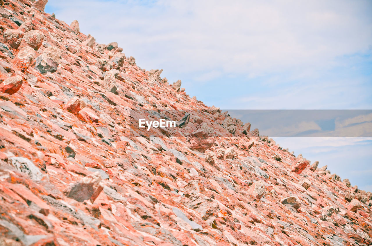 sky, cloud - sky, day, no people, nature, mountain, low angle view, beauty in nature, rock, solid, rock formation, outdoors, tranquility, rock - object, architecture, scenics - nature, tranquil scene, geology, brown, non-urban scene, eroded, roof tile