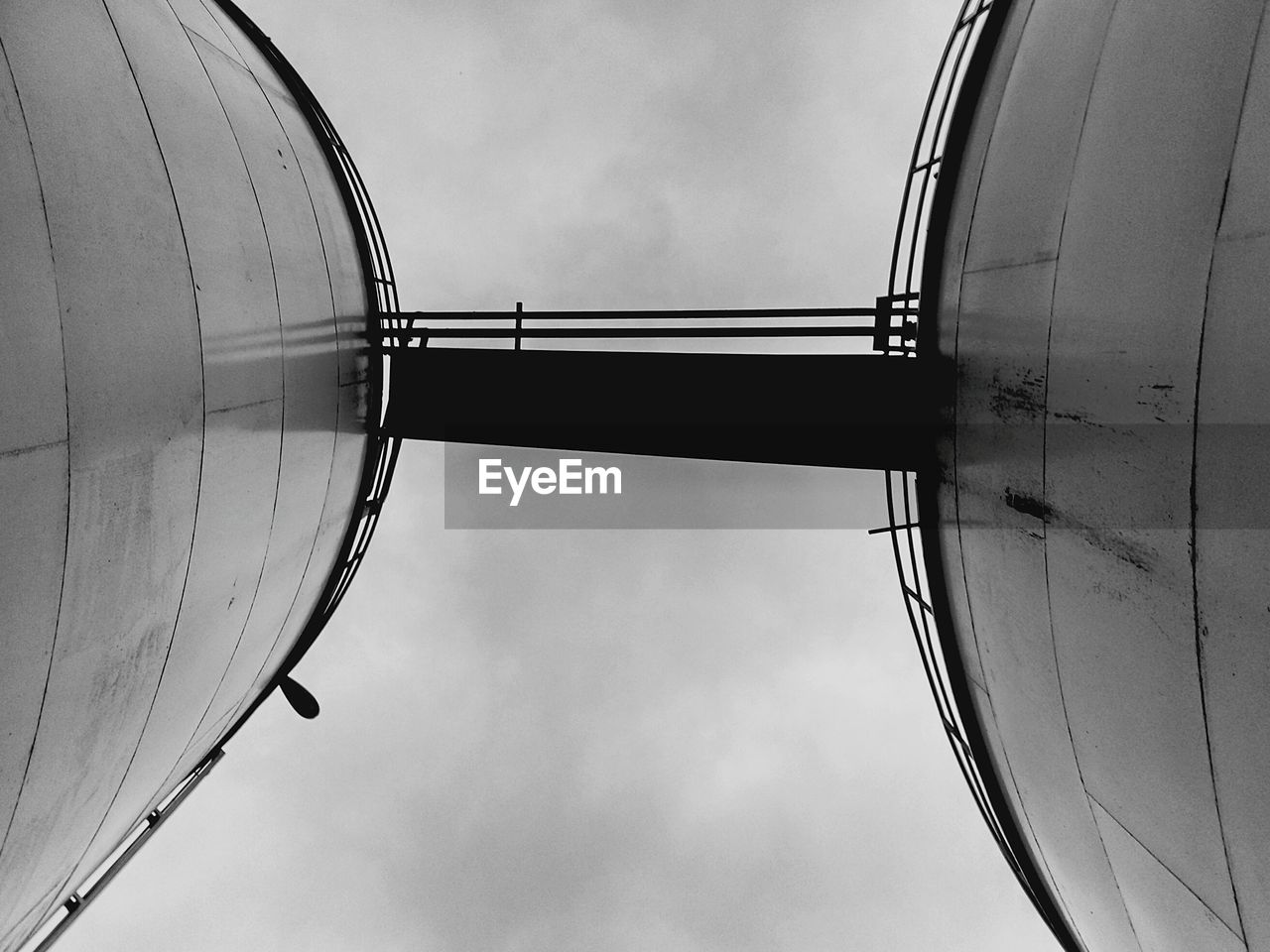 Low Angle View Of Bridge Connecting Industrial Tank Against Cloudy Sky
