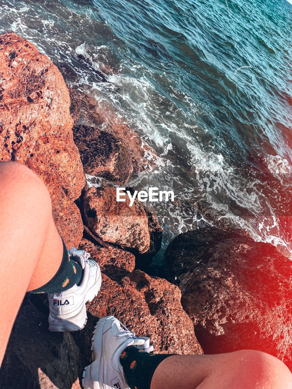 water, sea, rock, real people, solid, one person, rock - object, high angle view, aquatic sport, sport, nature, lifestyles, beach, day, motion, low section, land, leisure activity, outdoors