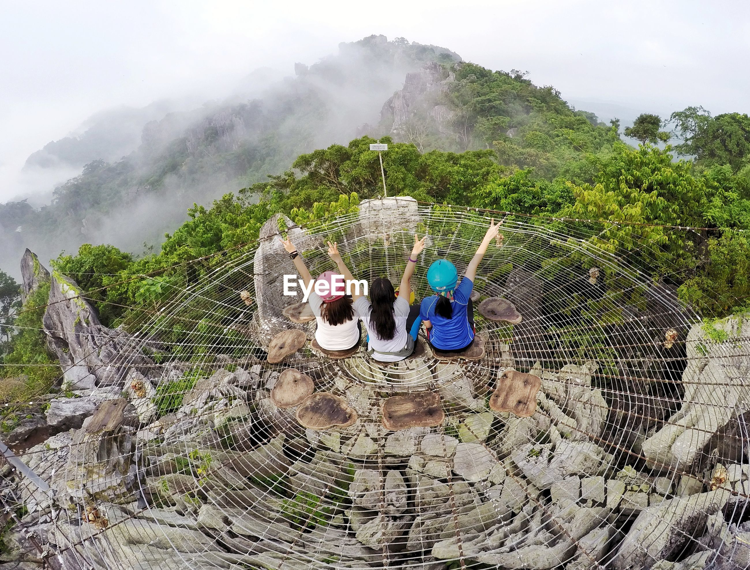 High angle view of female friends sitting on cliff against tree mountains