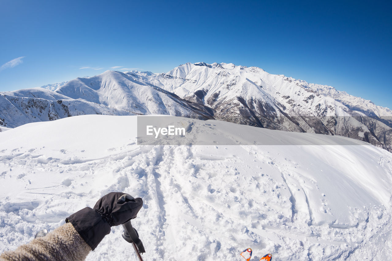 Low section of person on snowcapped mountain against clear blue sky