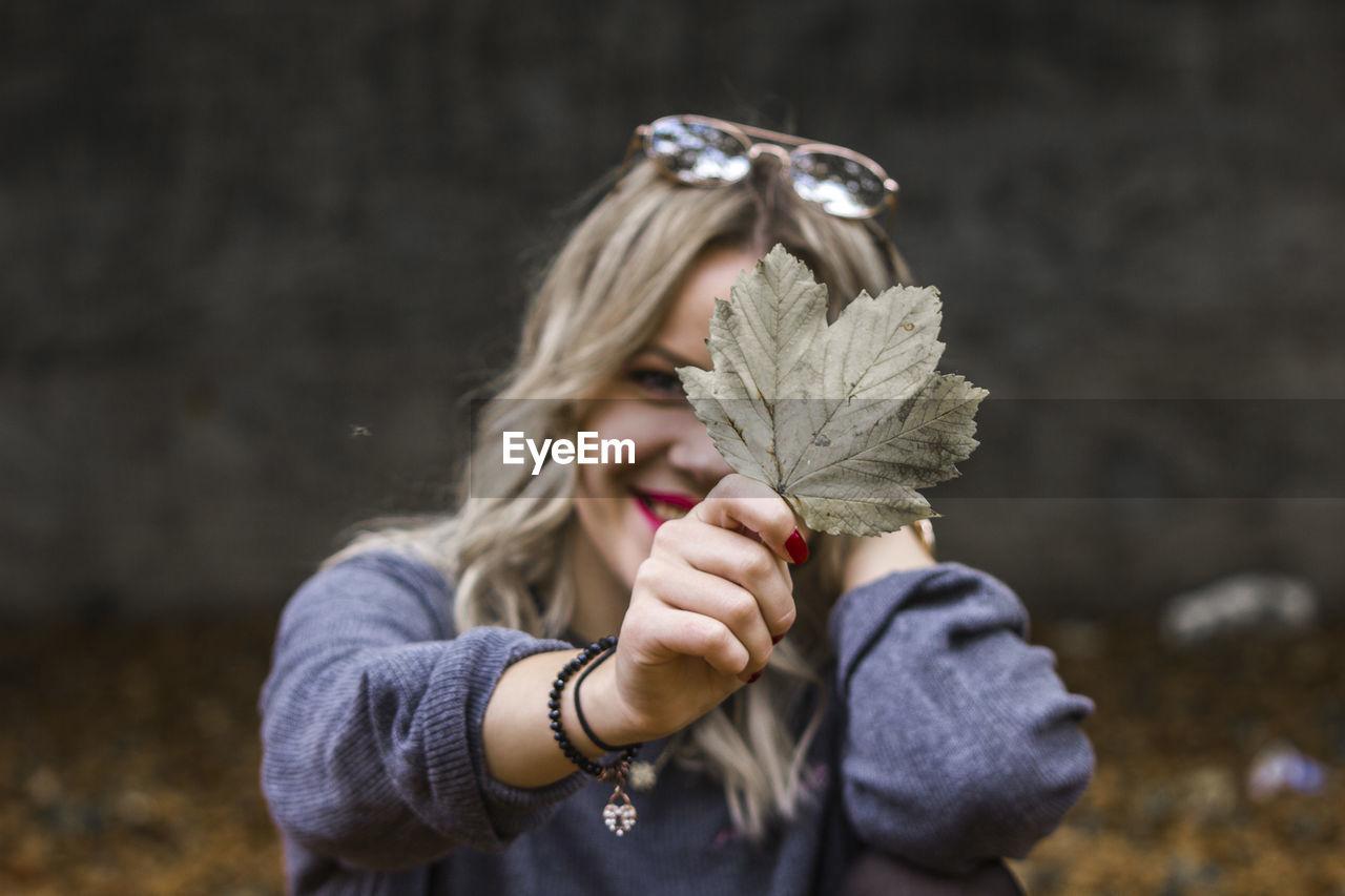 Close-up portrait of woman holding leaf