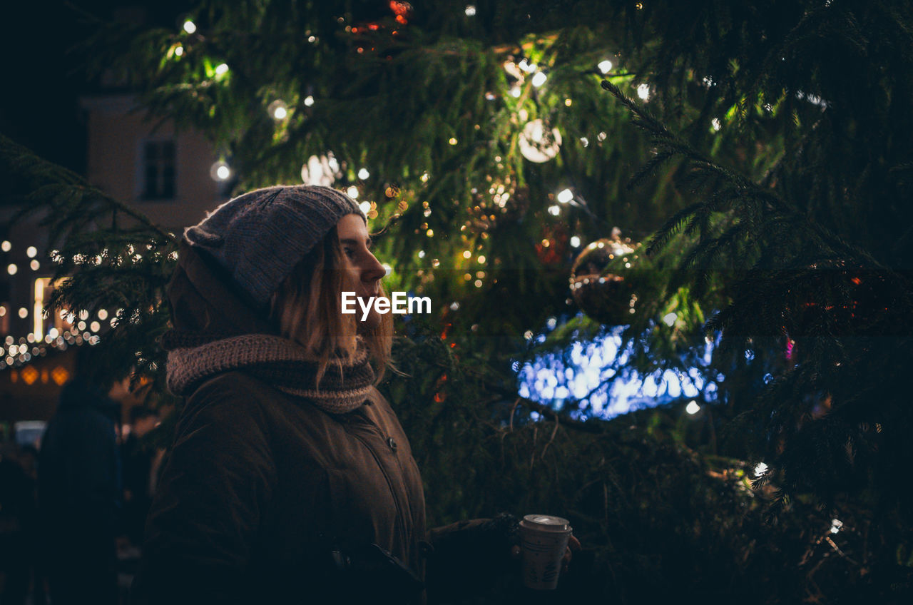 Woman on illuminated christmas tree at night