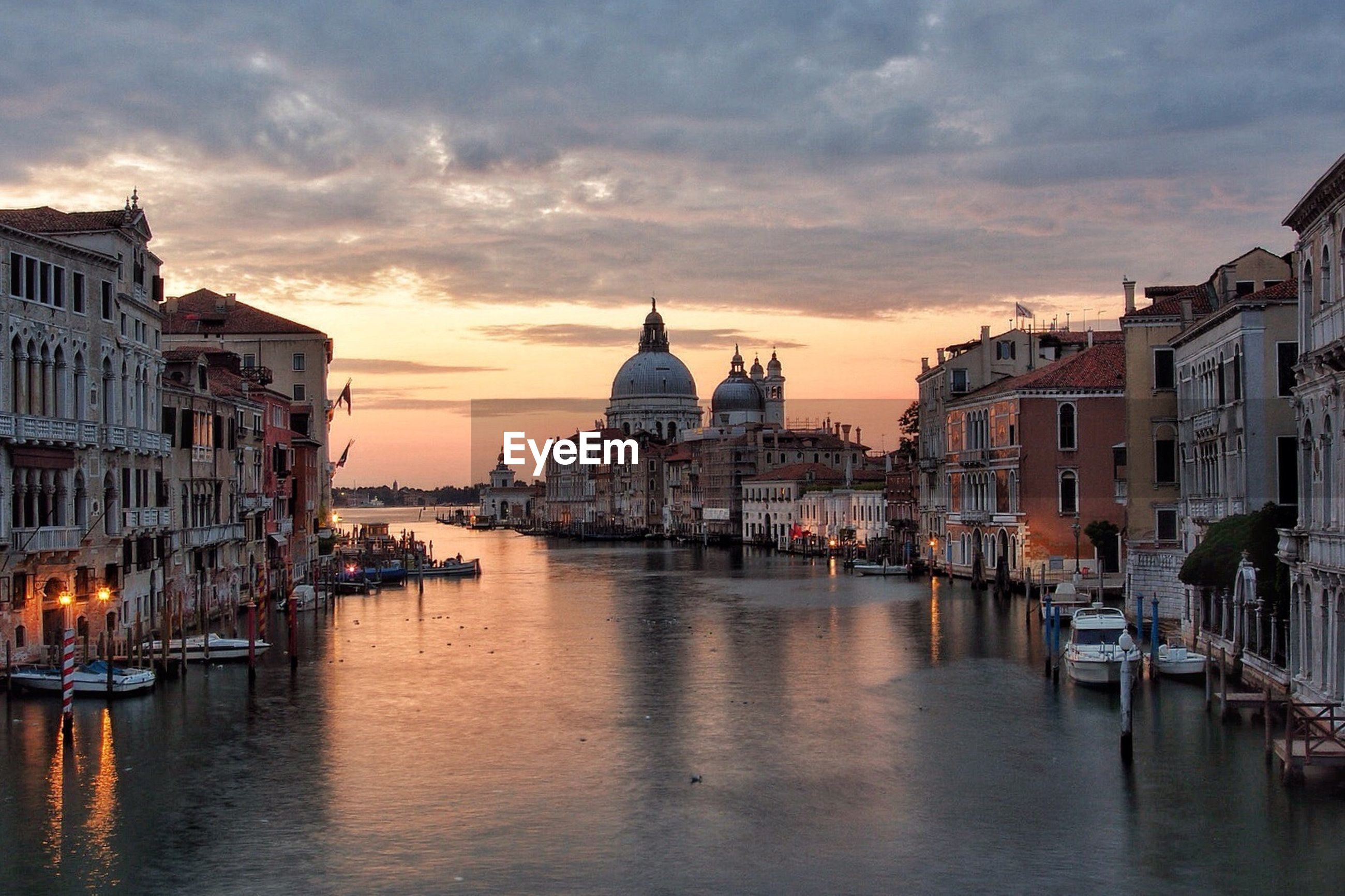 Grand canal by santa maria della salute against cloudy sky during sunset