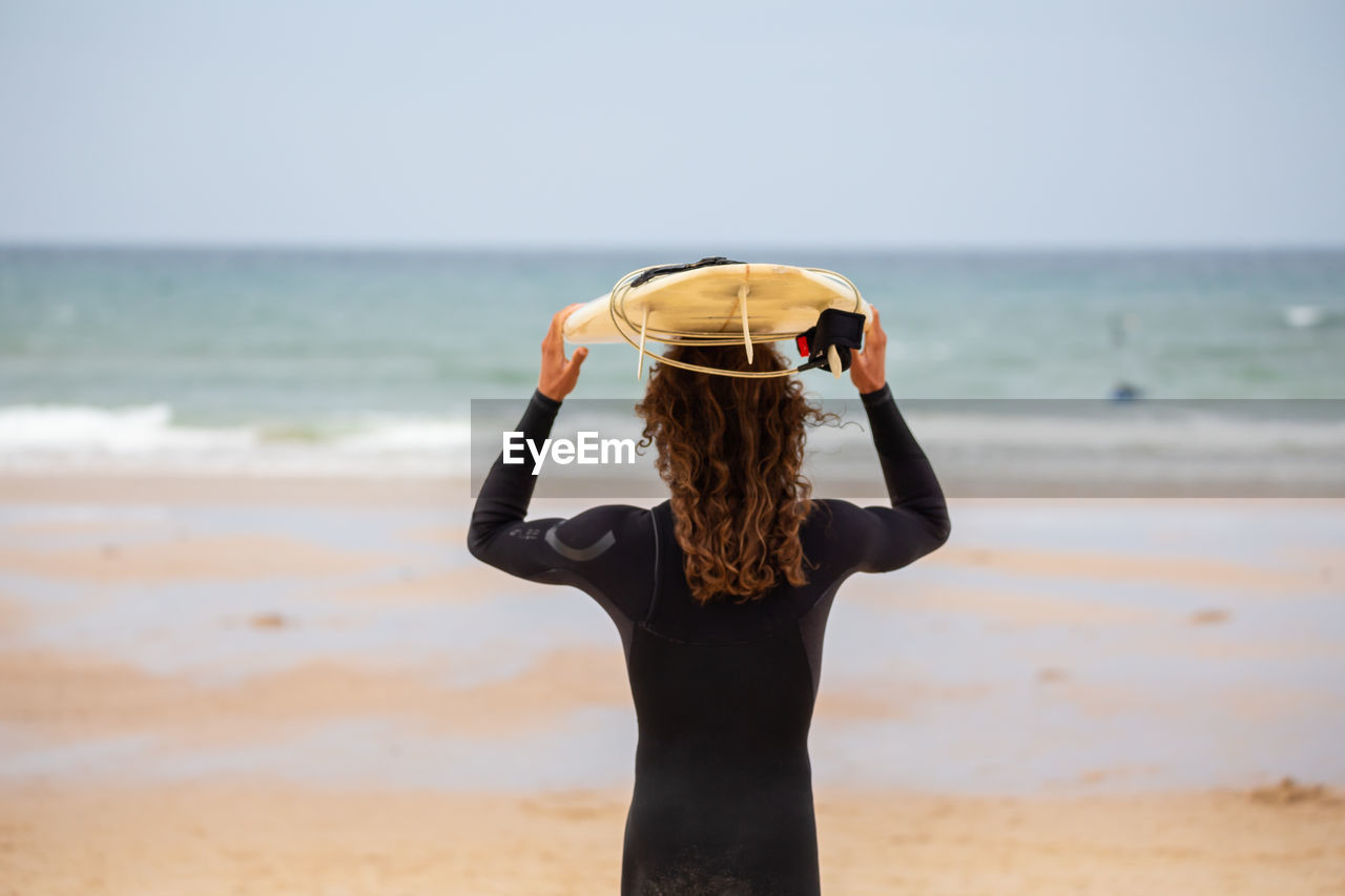 Rear view of man holding surfboard while standing at beach against sky