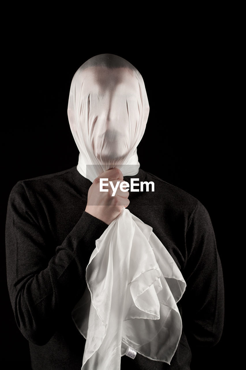 Man Covering Face With White Fabric Against Black Background