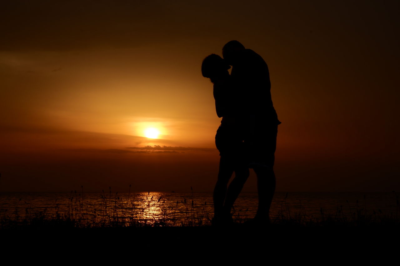 Silhouette couple kissing while standing at beach against sky during sunset