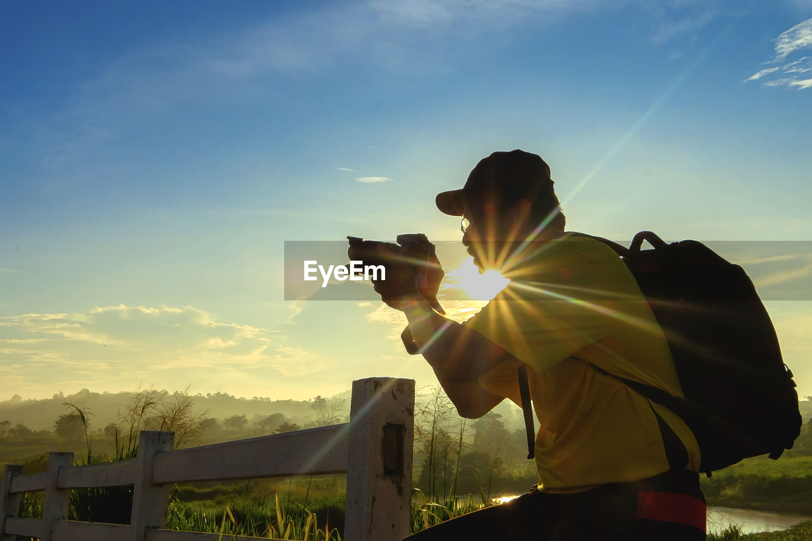 Man photographing on field against sky during sunset