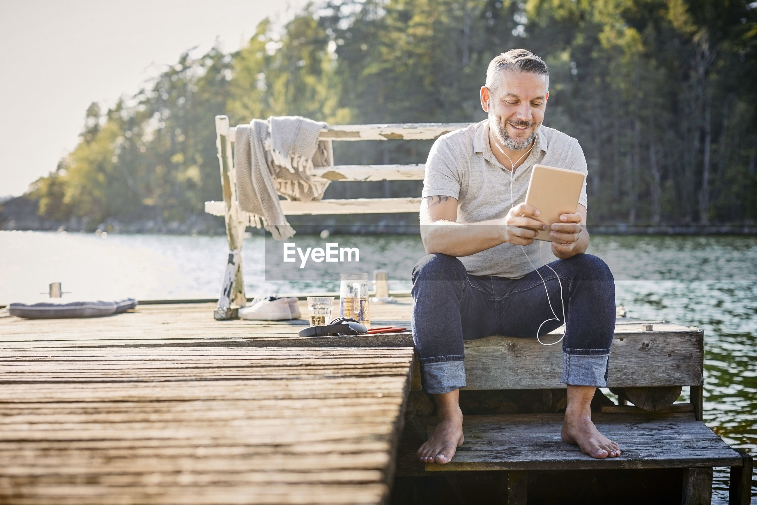 FULL LENGTH OF MAN USING MOBILE PHONE WHILE SITTING AT WOOD