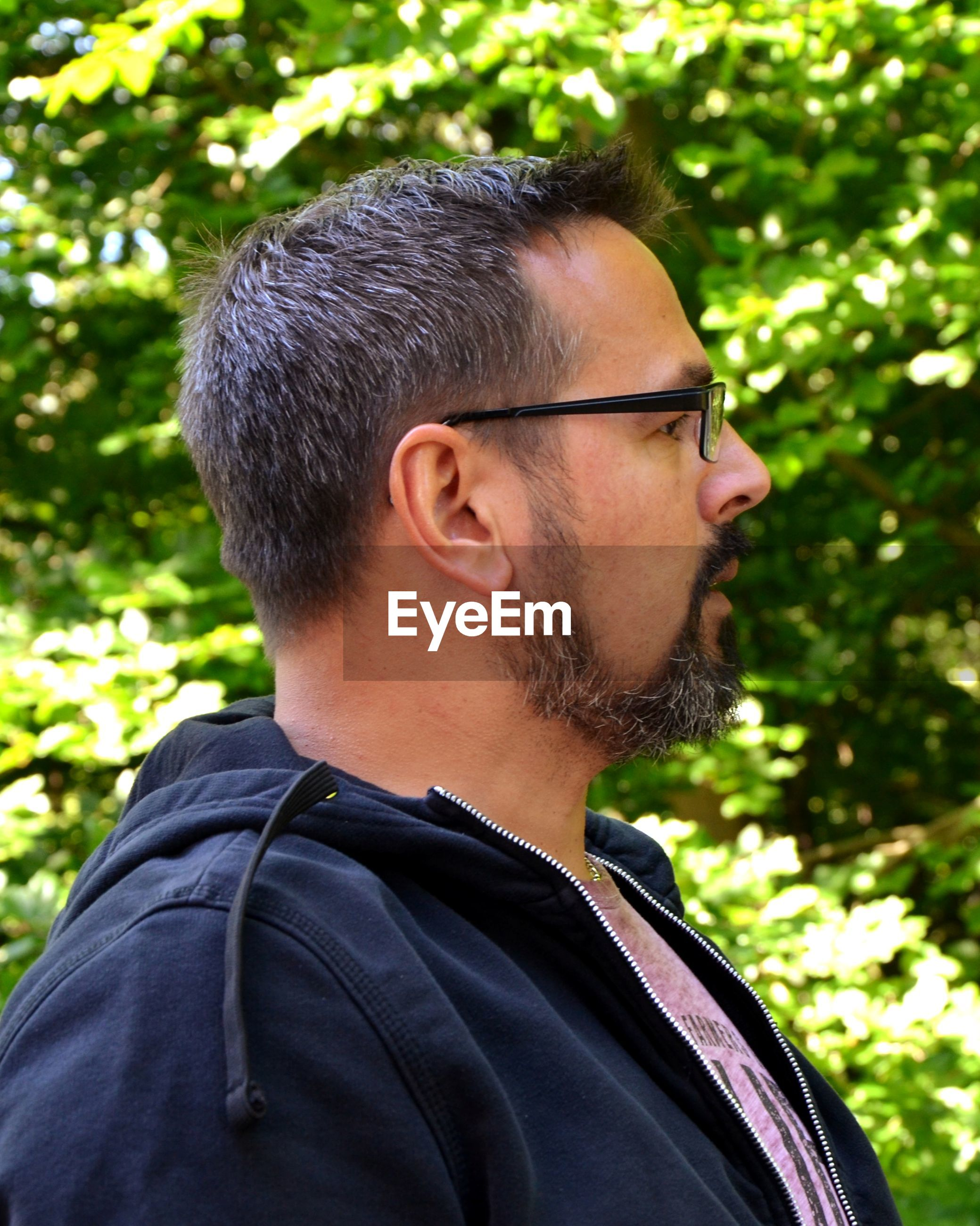 Man wearing eyeglasses looking away against plants