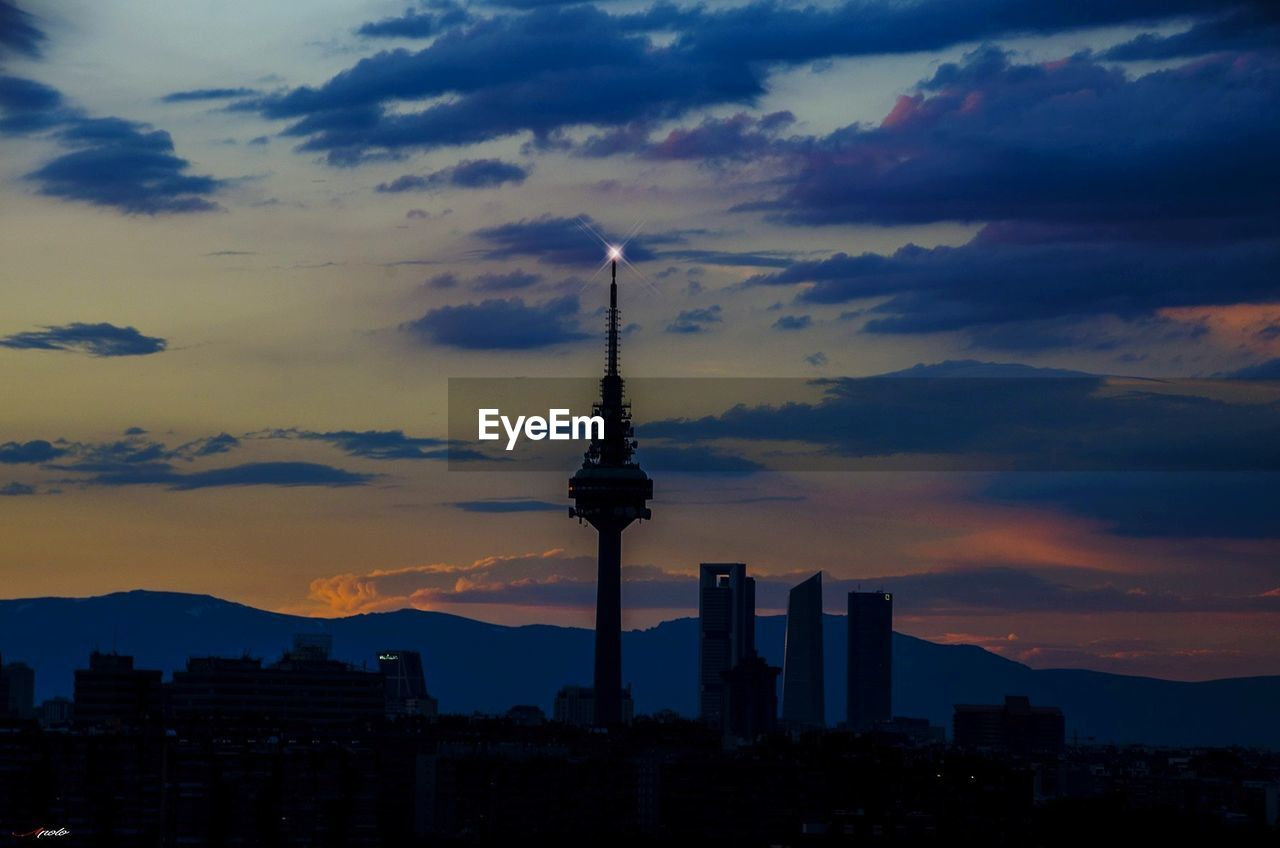 architecture, built structure, building exterior, sky, cloud - sky, tower, tall - high, building, city, sunset, travel destinations, silhouette, nature, travel, no people, skyscraper, office building exterior, cityscape, spire, modern, outdoors, global communications