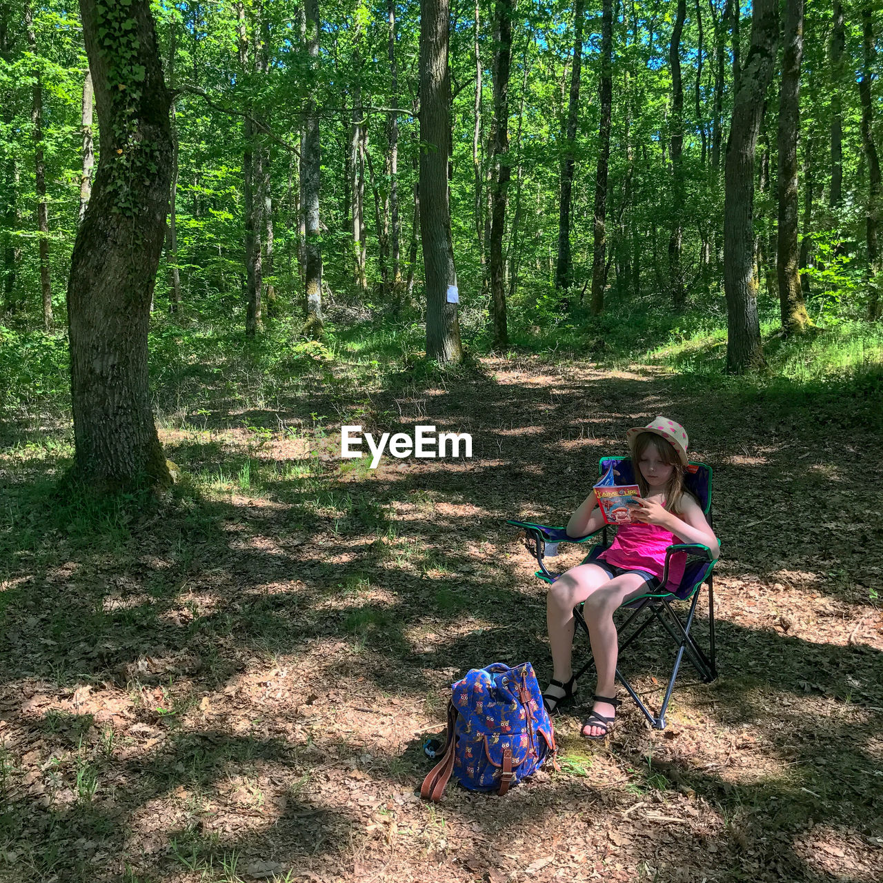 Girl sitting on chair against trees at forest