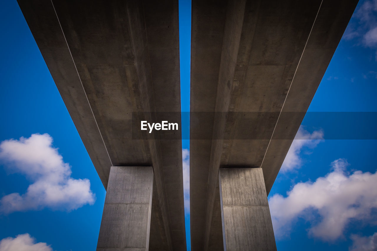 bridge, architectural column, sky, low angle view, bridge - man made structure, cloud - sky, architecture, connection, built structure, day, engineering, nature, below, blue, transportation, outdoors, strength, underneath, human body part, overpass
