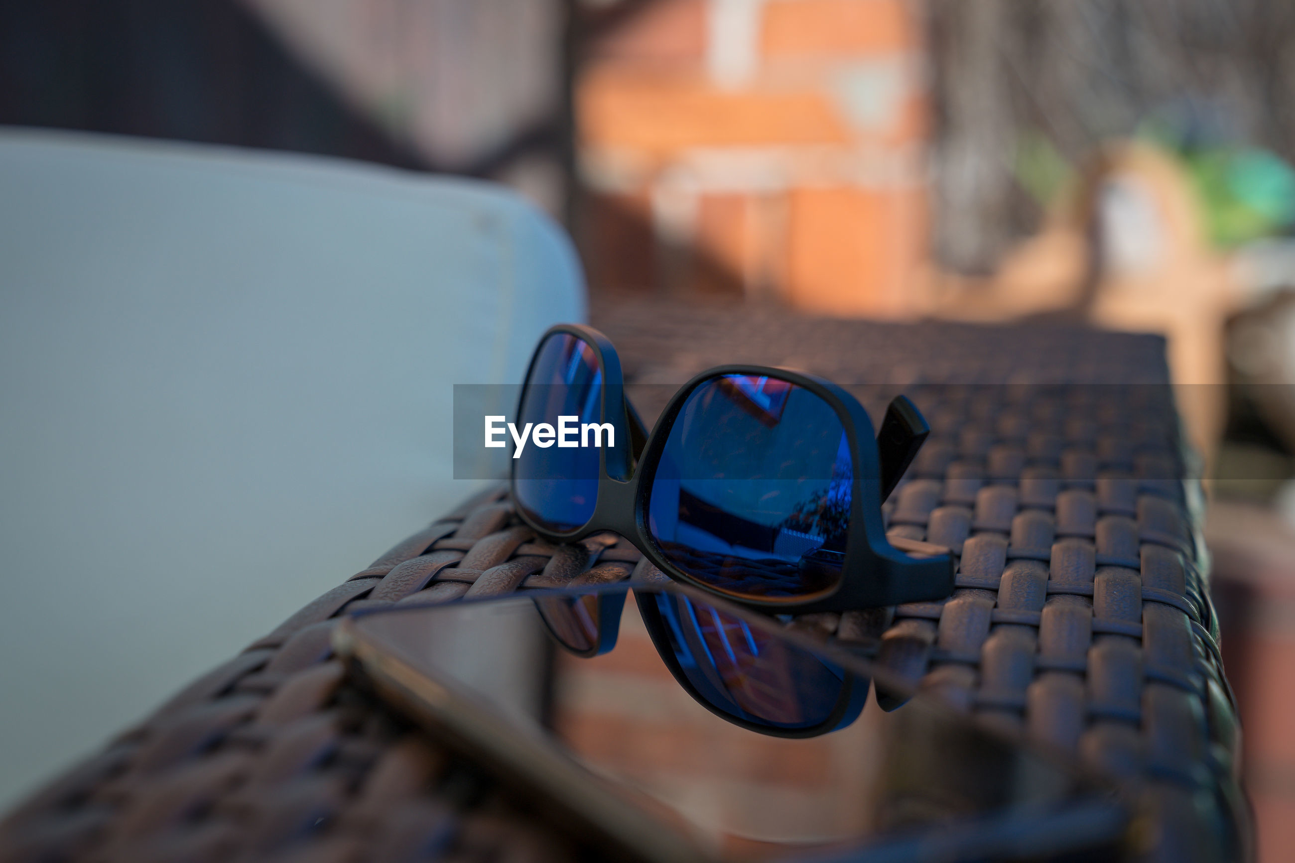 Close-up of sunglasses and mobile phone on table