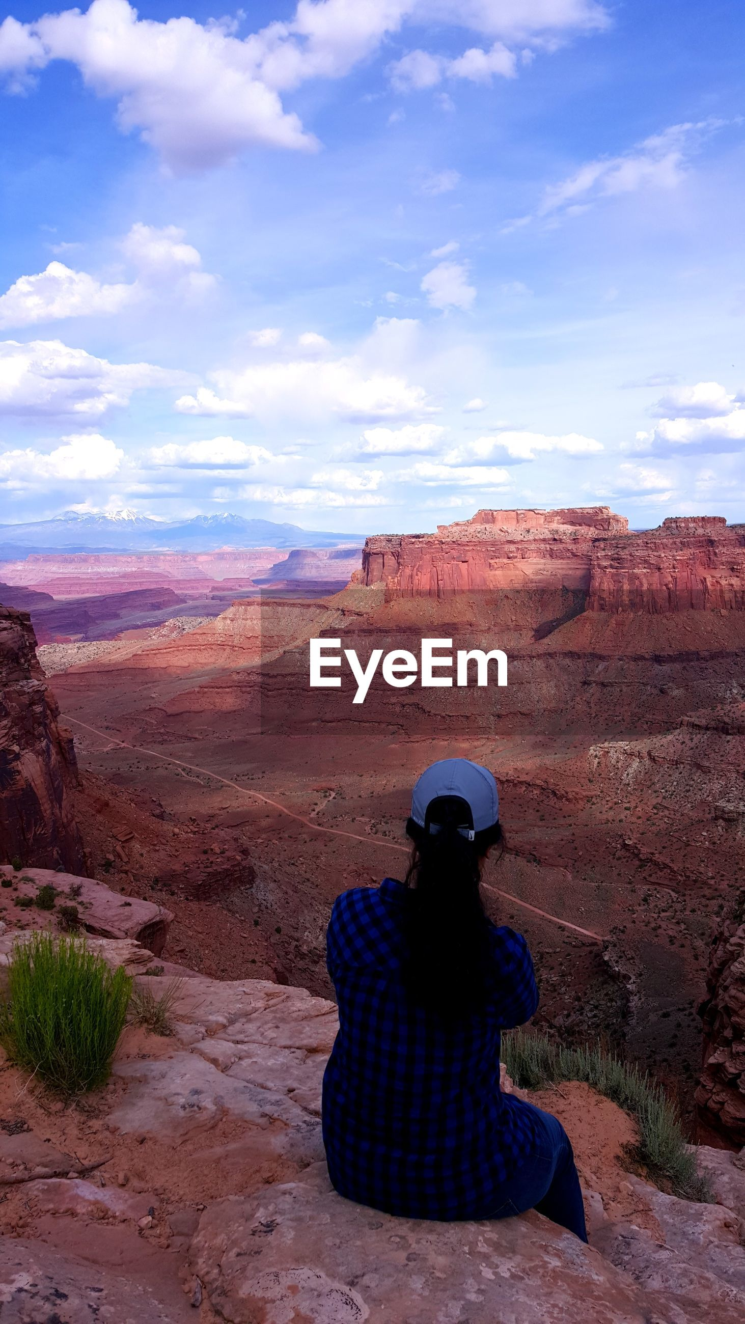 Rear view of woman sitting on rock formation at canyonlands national park