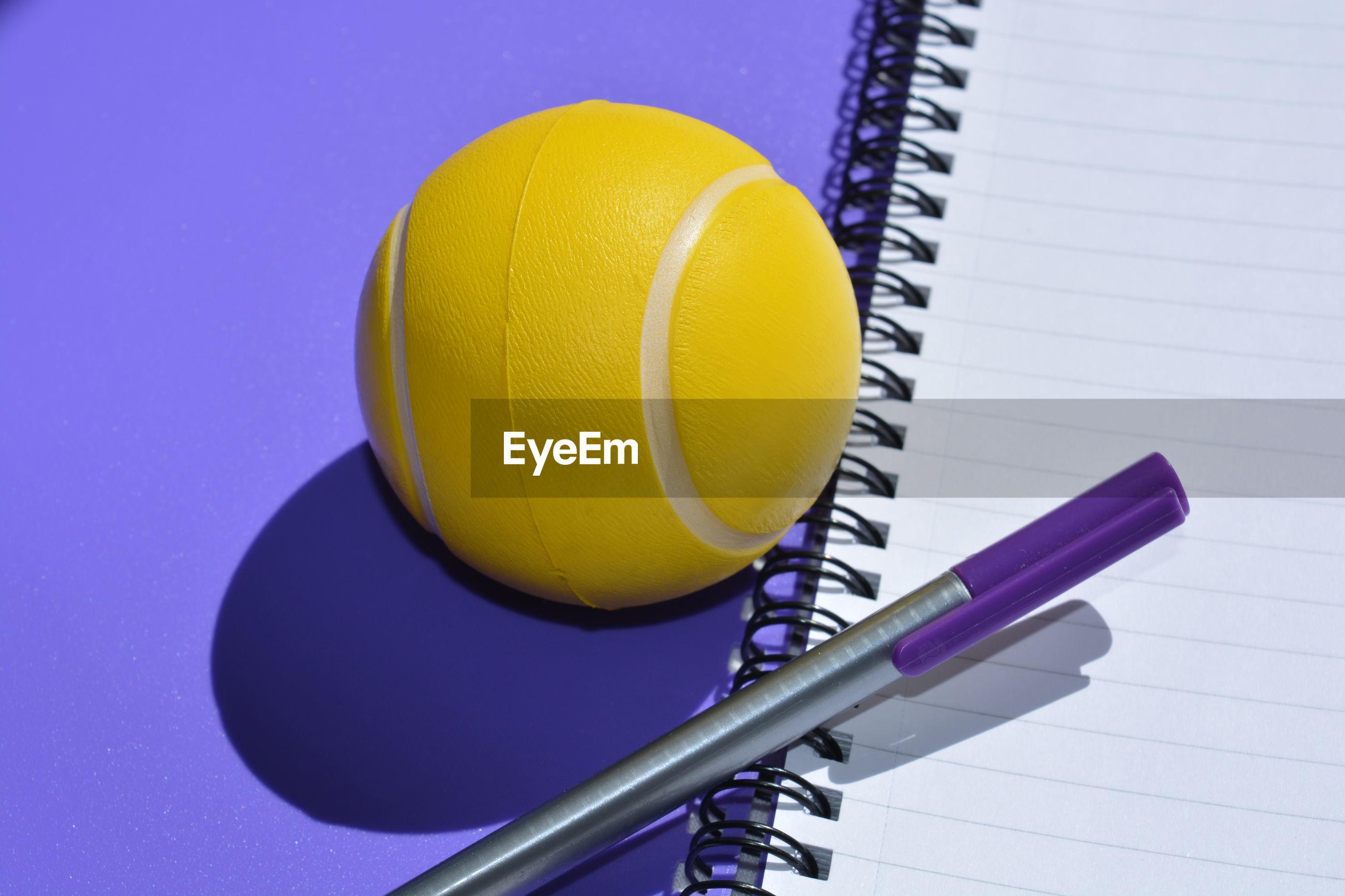 Stress ball and pen on an empty spiral bound notebook