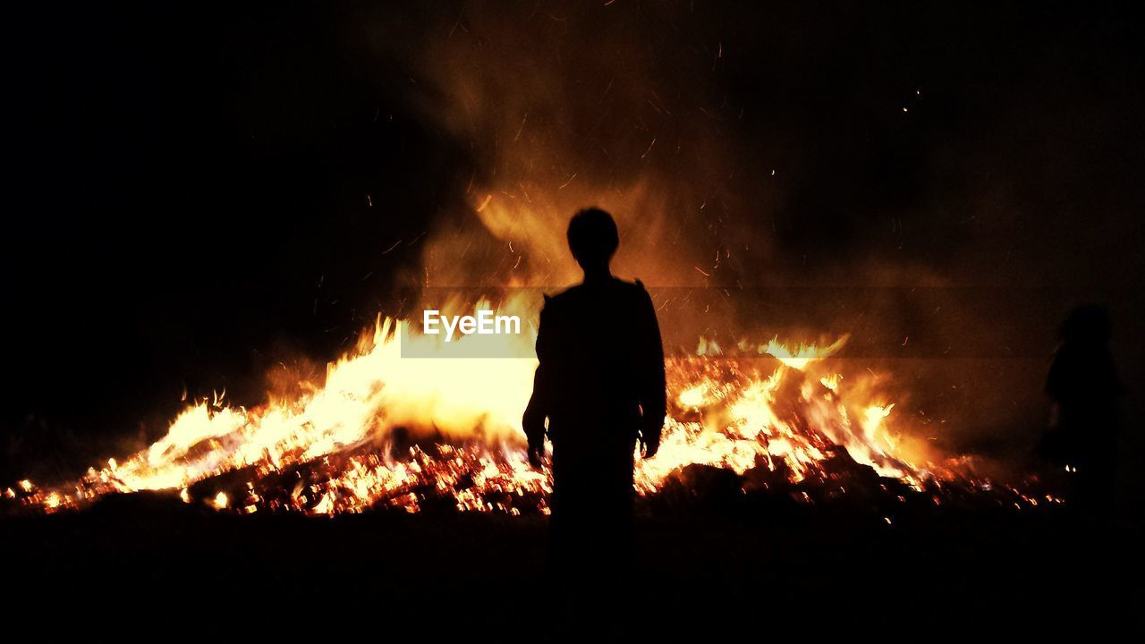 Silhouette Man Standing Against Bonfire