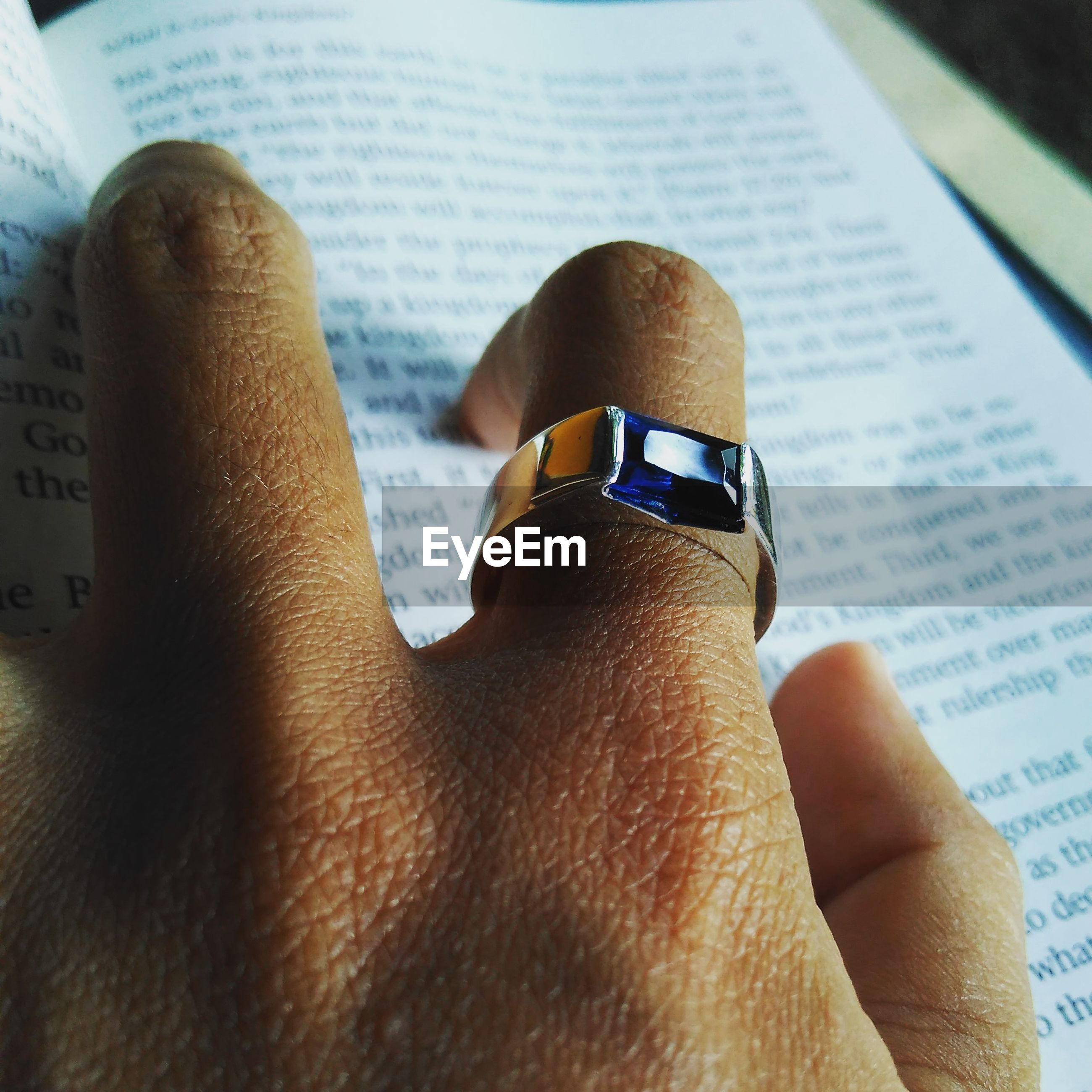 Cropped hand wearing ring on book
