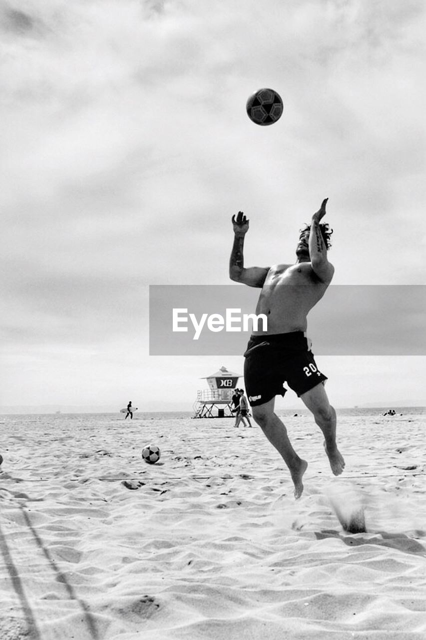 sea, beach, mid-air, real people, men, skill, full length, water, shirtless, jumping, leisure activity, one person, sky, sand, motion, vacations, lifestyles, horizon over water, outdoors, day, cloud - sky, sport, nature, playing, one man only, beauty in nature, only men, adult, people