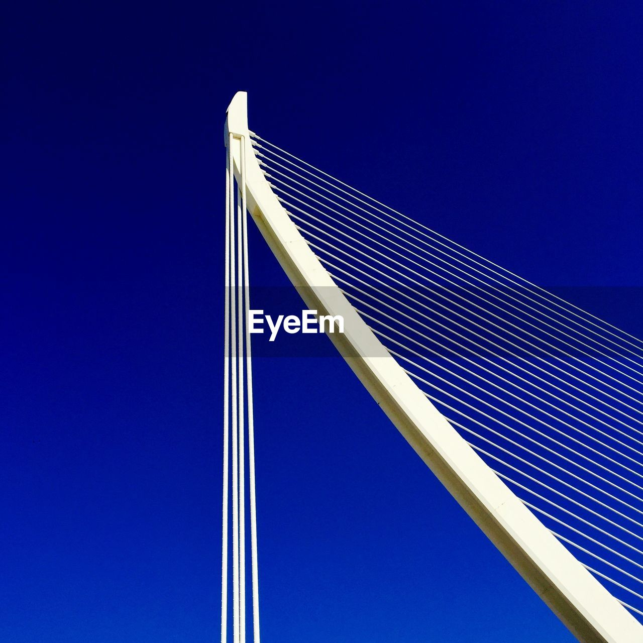 blue, sky, low angle view, clear sky, nature, no people, day, white color, copy space, outdoors, built structure, transportation, architecture, tall - high, connection, cable-stayed bridge, pattern, sunlight, fuel and power generation