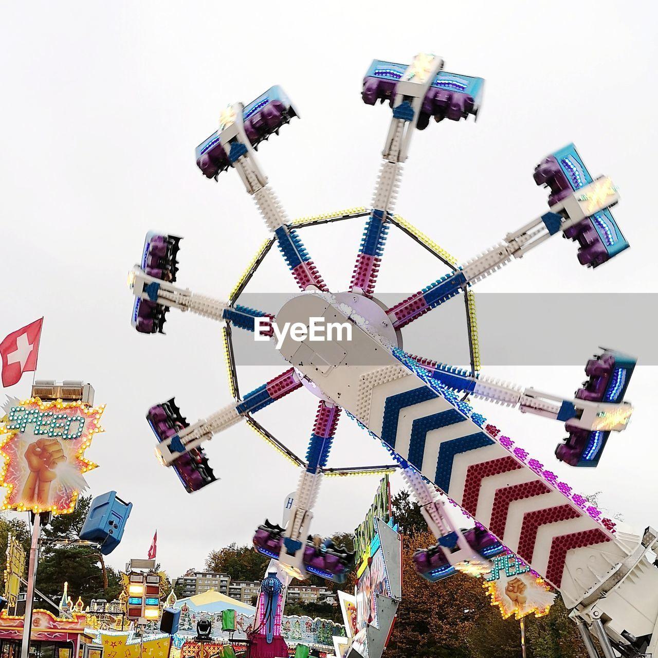 amusement park, amusement park ride, arts culture and entertainment, low angle view, sky, built structure, architecture, multi colored, leisure activity, enjoyment, group of people, decoration, fun, ferris wheel, building exterior, nature, carnival, hanging