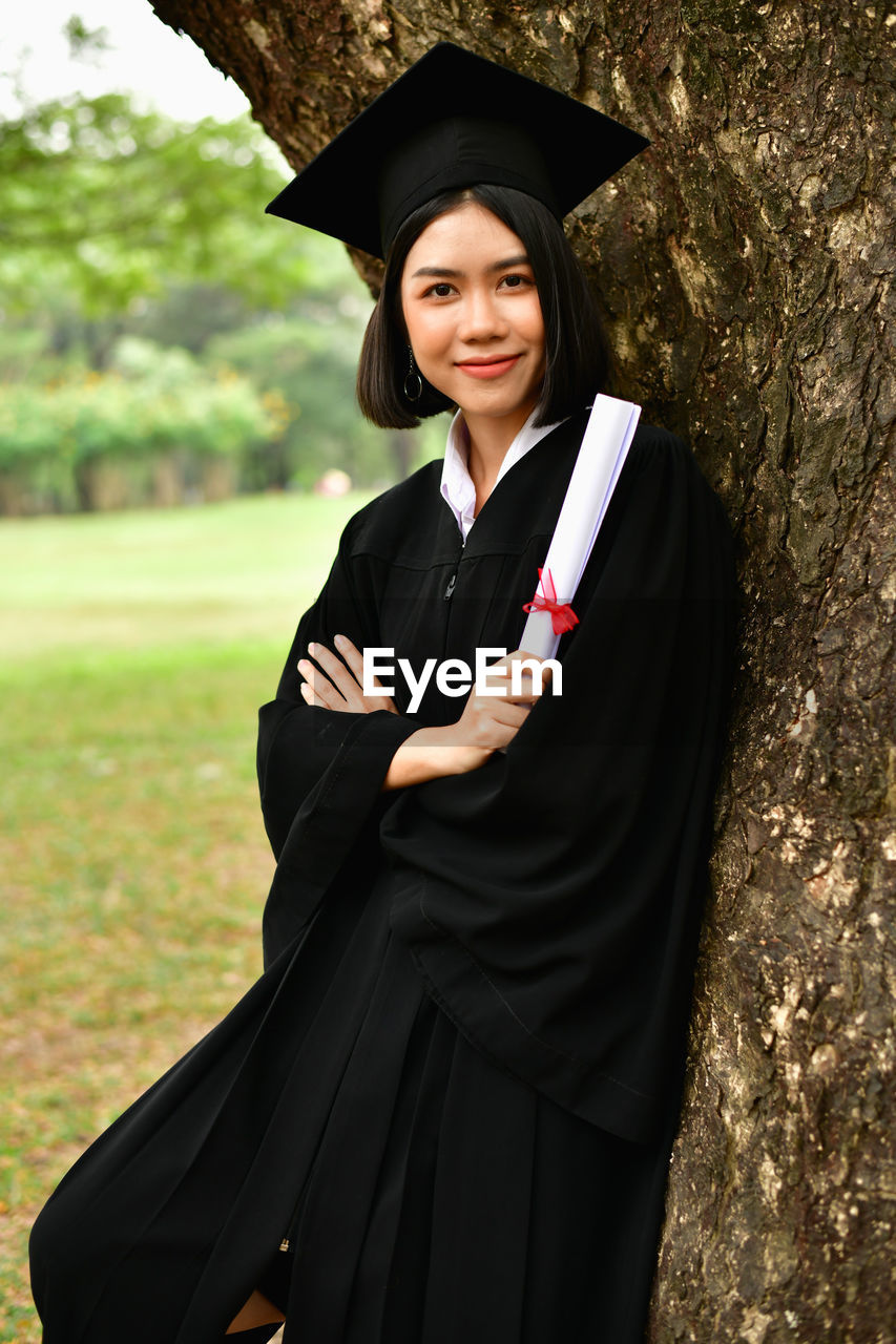 graduation gown, smiling, real people, graduation, portrait, young adult, one person, standing, looking at camera, happiness, mortarboard, achievement, education, young women, black color, front view, day, lifestyles, emotion, outdoors, beautiful woman