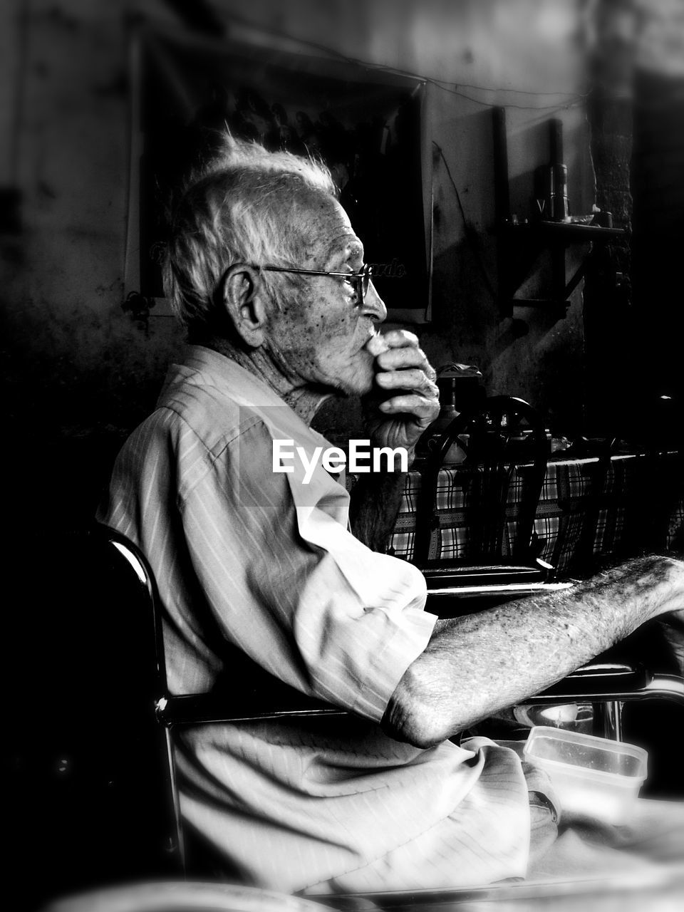 real people, senior adult, eyeglasses, one person, senior men, sitting, indoors, music, casual clothing, side view, concentration, lifestyles, glasses, technology, musical instrument, musician, day, human hand, close-up, people